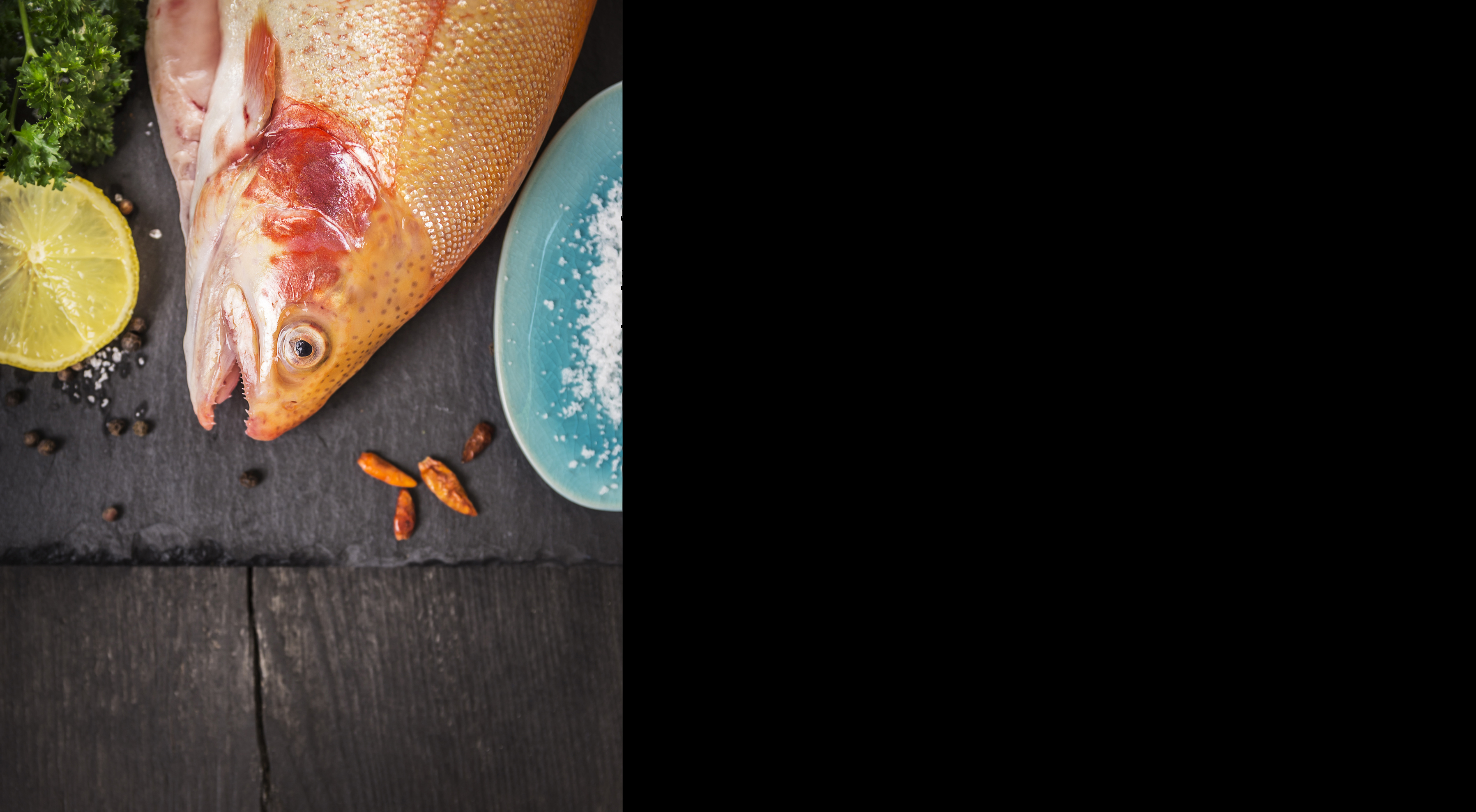 raw rainbow trout fish on wooden table, lemon and spices